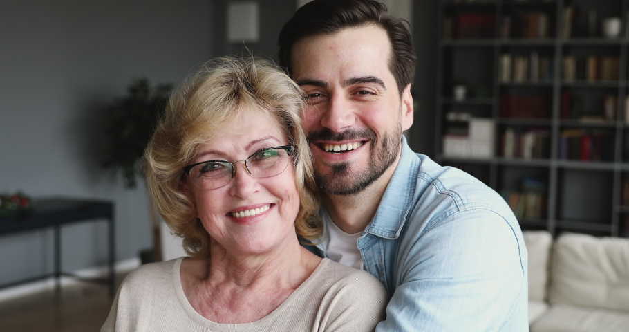 Happy affectionate older mom and adult son embracing smiling looking at camera. Relaxed millennial young man hugging loving 60s mother posing for 2 two age generations family closeup portrait indoors | Shutterstock HD Video #1047036850