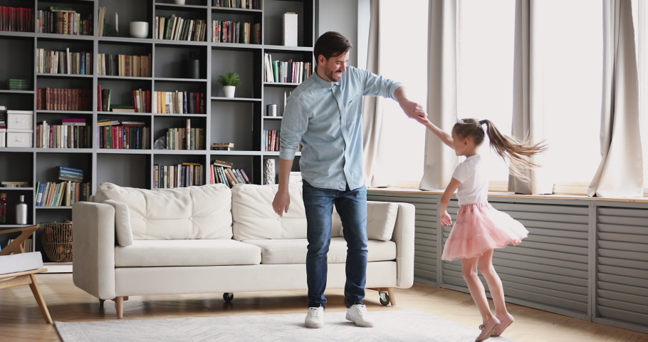 Affectionate loving young dad teaching dancing with cute small child. Daughter princess wear crown skirt having fun in modern living room playing ball together enjoy sweet funny activity at home. Royalty-Free Stock Footage #1047036856