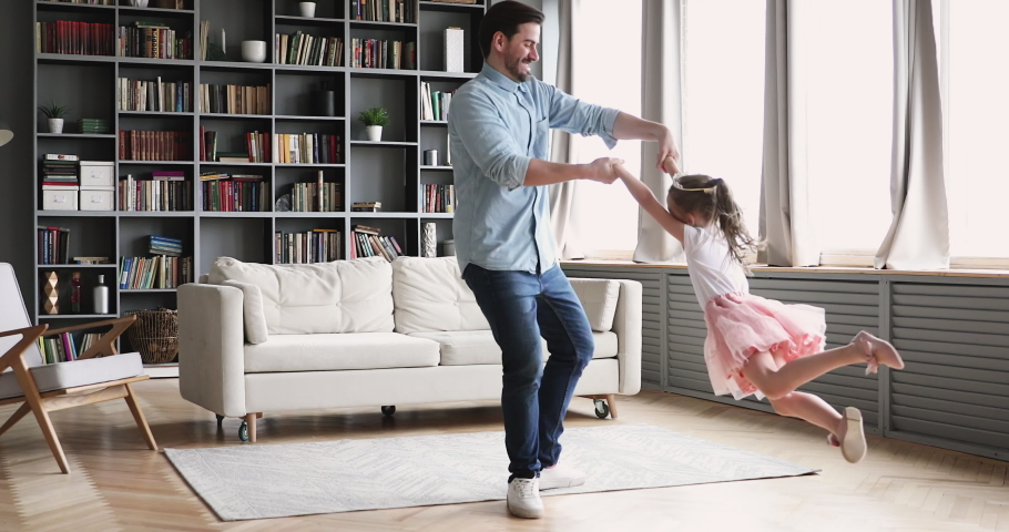 Loving father having fun spinning dancing with cute little child daughter princess wear crown in modern living room. Happy dad and small kid girl playing enjoying funny active dance together at home