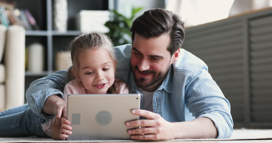 Happy family adult parent dad and small daughter having fun using digital tablet lying on floor at home. Cute child girl learning technology talking with father teaching kid look at pad screen at home Royalty-Free Stock Footage #1047036883