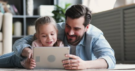 Happy family adult parent dad and small daughter having fun using digital tablet lying on floor at home. Cute child girl learning technology talking with father teaching kid look at pad screen at home
