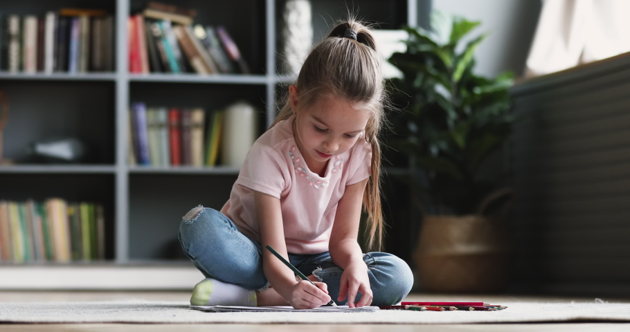 Cute concentrated little kid girl draw color pencil play alone on floor. Pretty preschool child coloring picture at home enjoy creative activity relax sit on carpet, children playtime education concep