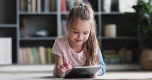 Curious cute preschool kid girl using digital tablet technology device lying on carpet floor alone. Small child hold pad computer surfing internet play game at home. Children tech addiction concept