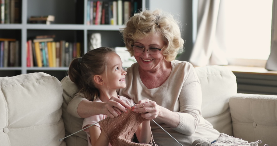 Happy senior old adult granny teaching small cute granddaughter learning knitting needles.Two generations family grandparent and little grandchild, having fun enjoying handcraft hobby concept at home Royalty-Free Stock Footage #1047036922