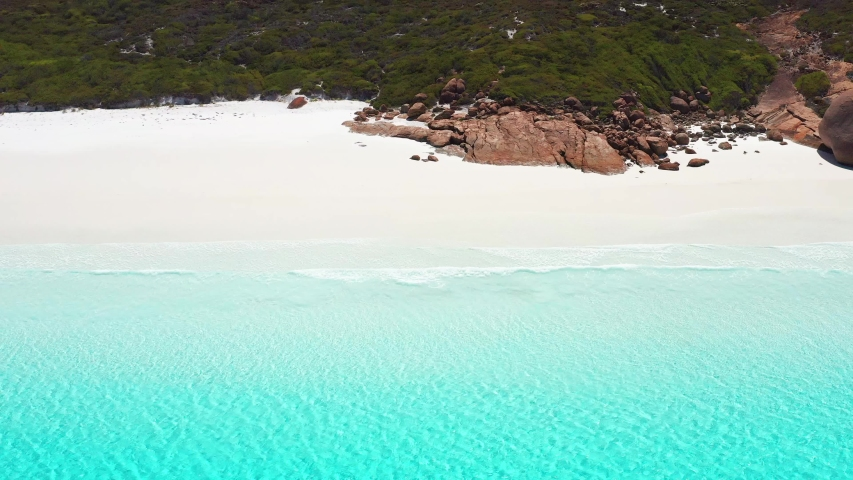 Aerial high angle of turquoise blue water, white sand, granite rocks, and waves rolling in onto one of Australia's whitest beaches - Lucky Bay. Taken at the far east end of the bay / beach. | Shutterstock HD Video #1047044416