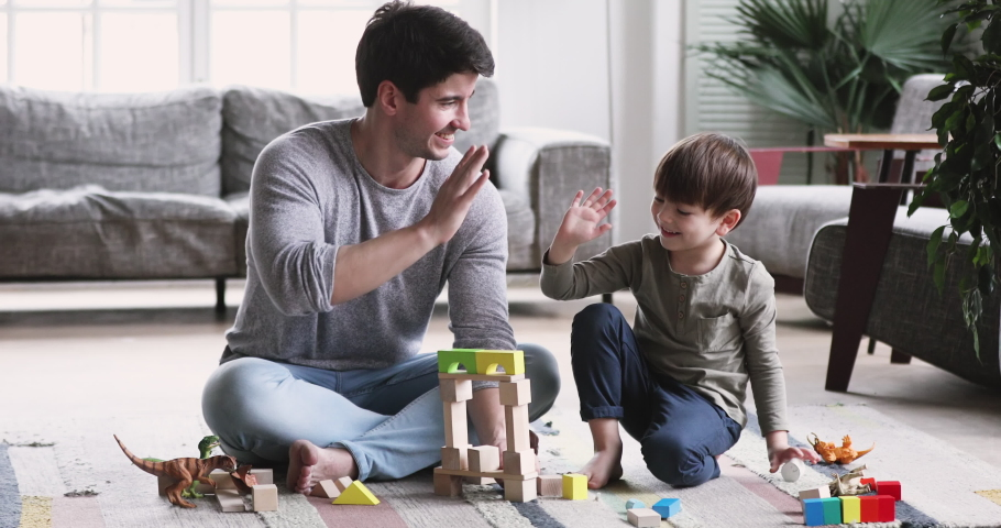 Happy young adult parent dad and child son play toys sit on floor carpet at home. Caring father having fun help cute kid build tower of wooden blocks. enjoy game activity give high five in living room
