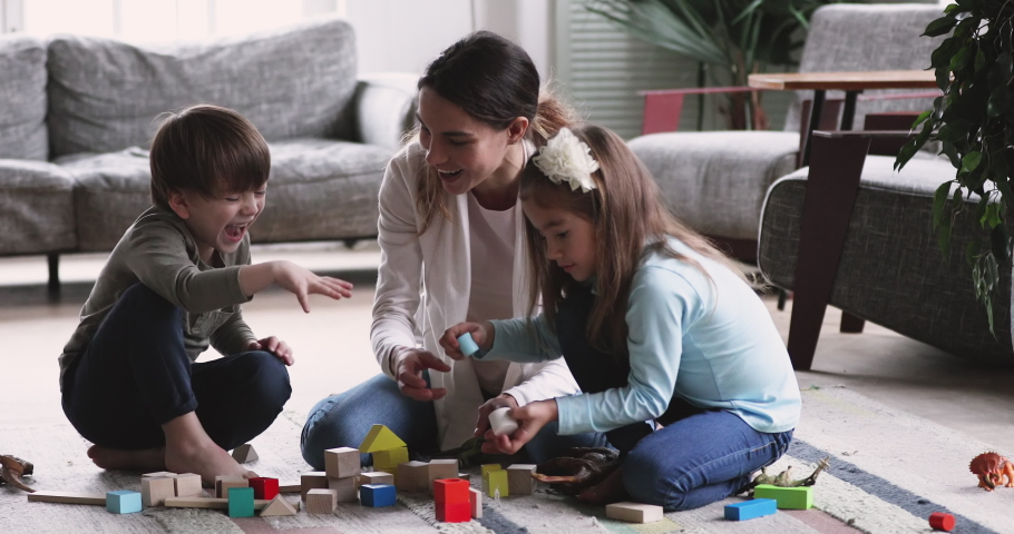 Happy young adult mother nanny playing with two cute small kids, having fun sit on floor carpet at home. Playful mum helping preschool children building tower of wooden blocks in living room
