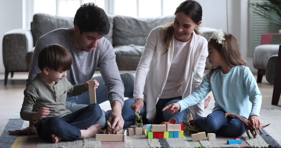 Happy carefree family, young parents mom and dad having fun play dinosaurs wooden blocks with two small preschool children. Funny kids sit on floor carpet enjoy free time game in living room together Royalty-Free Stock Footage #1047050974