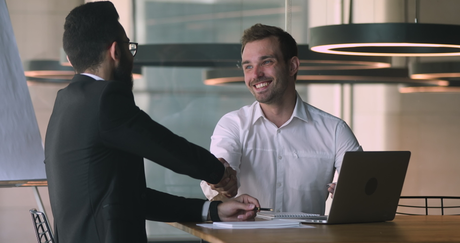 Confident caucasian male financial advisor bank worker broker explaining deal benefits, showing presentation on computer to focused arabic businessman, shaking hands after making agreement in office. Royalty-Free Stock Footage #1047050998