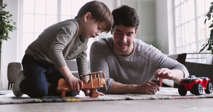 Young father and cute small kid son playing funny racing game relax on carpet floor at home. Happy male family adult dad and little child boy having fun with toy car plane engaged in leisure activity