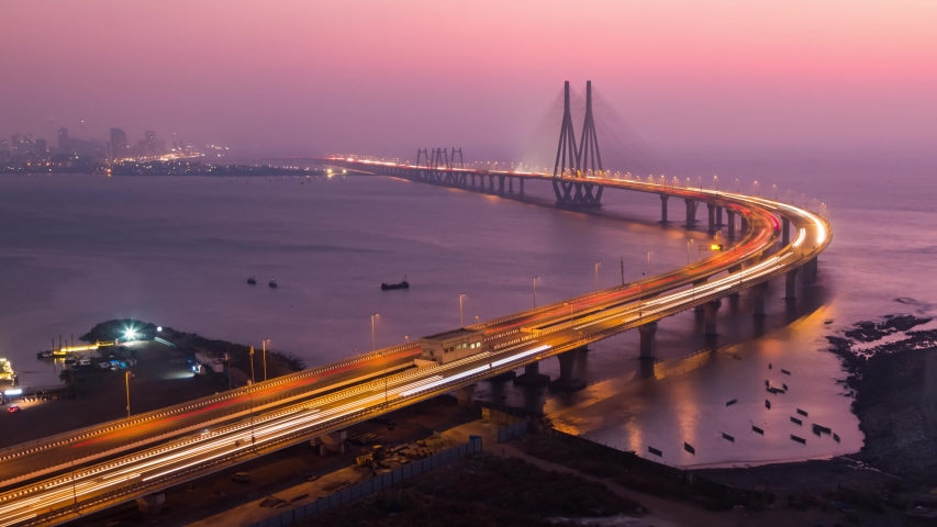 Day to Night Panning Tilting Down Sunset Timelapse of the car traffic on the famous Bandra Worli Sea Link Bridge, Mumbai, Maharashtra, India.