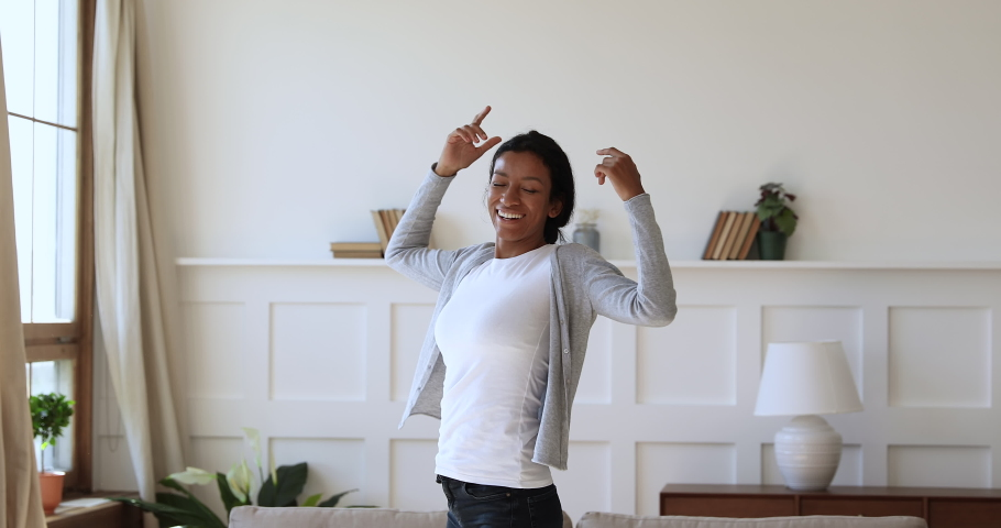Overjoyed young african woman feeling joyful, thanking god for good luck. Thankful mixed race girl enjoying freedom alone at home. Excited homeowner spinning with stretched arms, real estate concept. Royalty-Free Stock Footage #1047056845