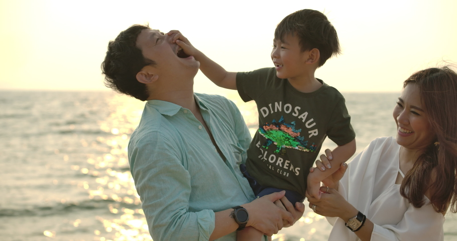 Happy parents kissing their son in both cheeks. Young asian father and mother are holding their cute child in their hands and kissing him from both sides on the beach at sunset.