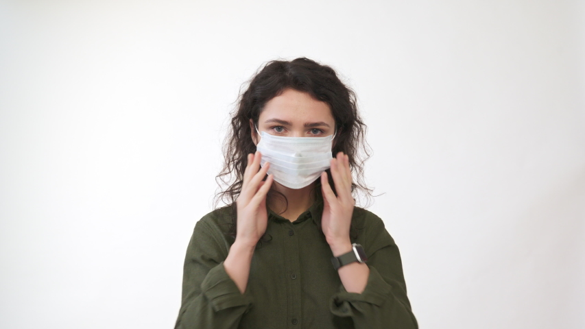 Young woman coughing. Wearing medical mask looking at camera. isolated on white  background. Close up front portrait. Health concept. 4k | Shutterstock HD Video #1047081391