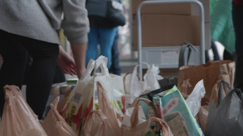 Volunteers fill grocery bags full of food  donations, as they do a good deed for the needy, elderly, and less fortunate by donating their time and food. Hands, shallow depth