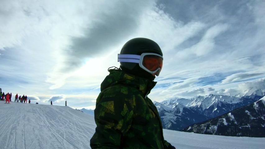 A boy snowboarding holding a selfie stick | Shutterstock HD Video #1047091930