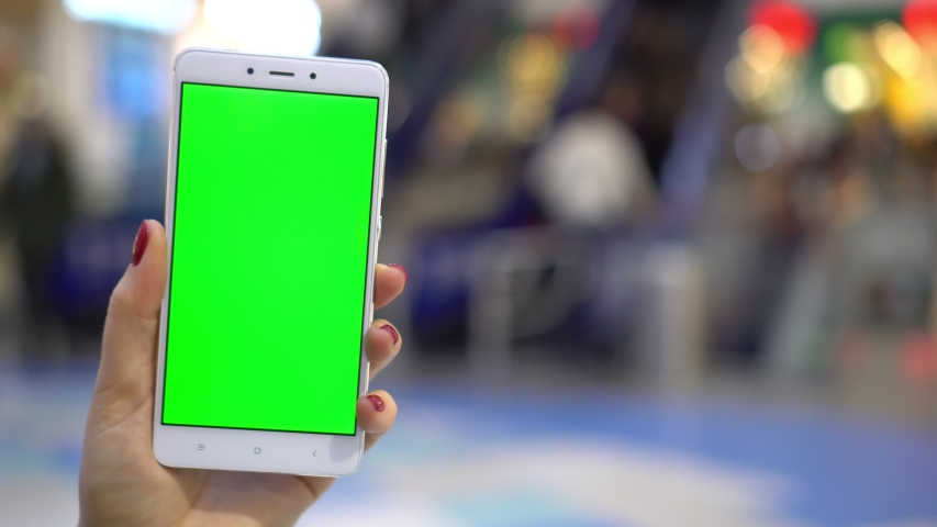 Woman focused on her smartphone while displaying a green screen. Concentrated at the screen of her device. Chroma key slide shot | Shutterstock HD Video #1047099829