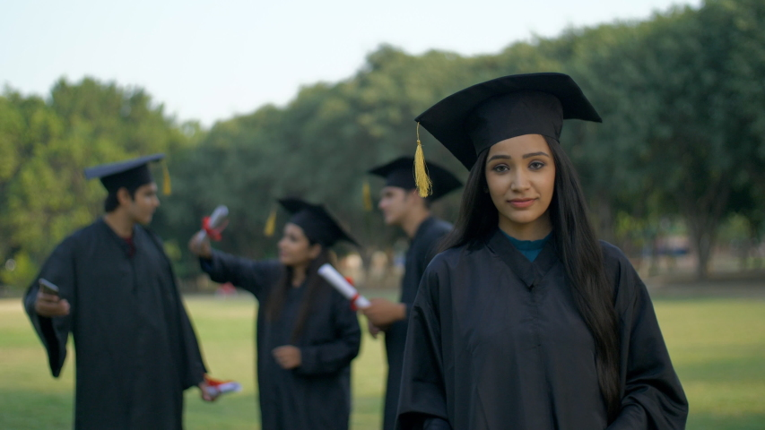 Young graduated girl holding her graduation degree in pride - convocation ceremony. Attractive Indian graduate posing towards the camera with a big smile on her face in graduation gown and hat - co... Royalty-Free Stock Footage #1047111781
