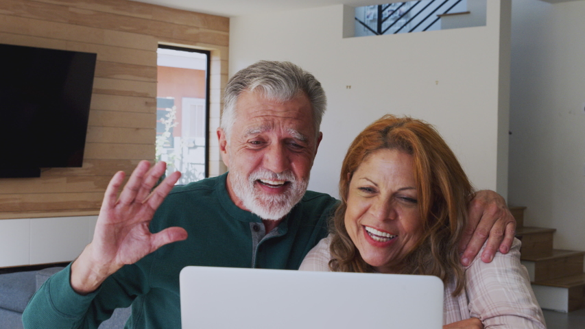 Senior Hispanic Couple At Home With Laptop Having Video Chat With Family | Shutterstock HD Video #1047116383