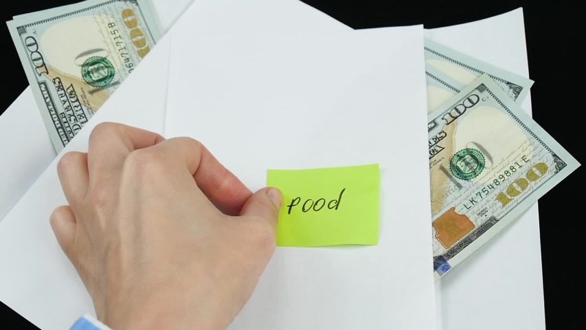 Hand close-up pasting a sticker with the words food on the envelope with money. The person distributes the personal budget, money for food expenses. The concept of social policy and financial well Royalty-Free Stock Footage #1047116644