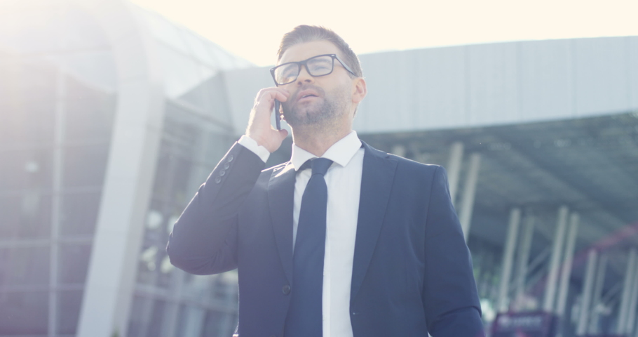 Young Caucasian attractive businessman in glasses walking the street and talking on mobile phone. Handsome man in suit and tie speaking on cellphone while stepping outdoors.   Shutterstock HD Video #1047117439