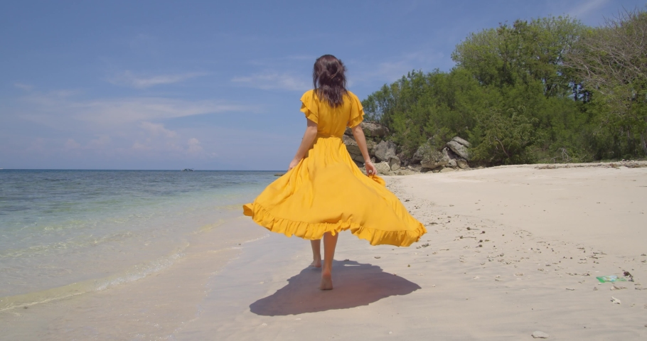 Brunette in yellow dress walking along the ocean beach, nice back shot taking the ocean air and admiring seascape | Shutterstock HD Video #1047117778