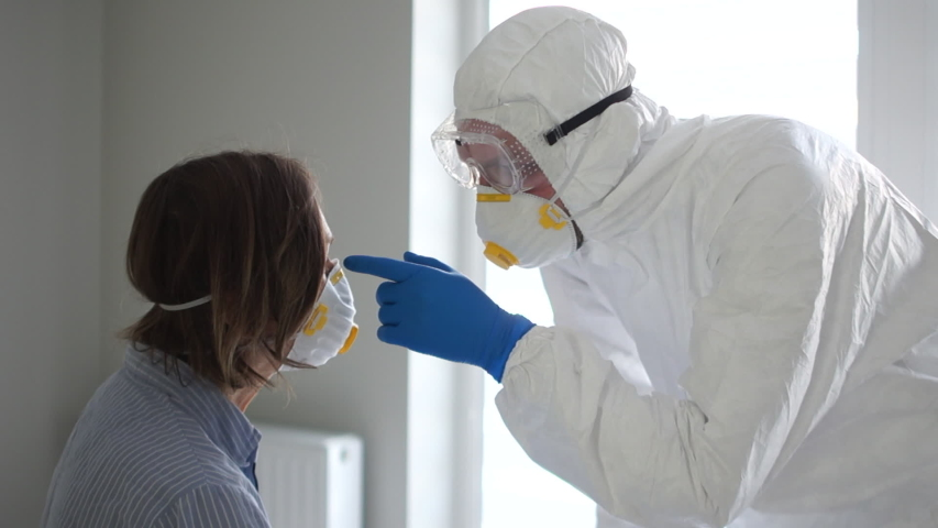 Close up portrait of a masked man in a protective suit examines an infected woman. Symptoms of Coronavirus Covid19 | Shutterstock HD Video #1047124144