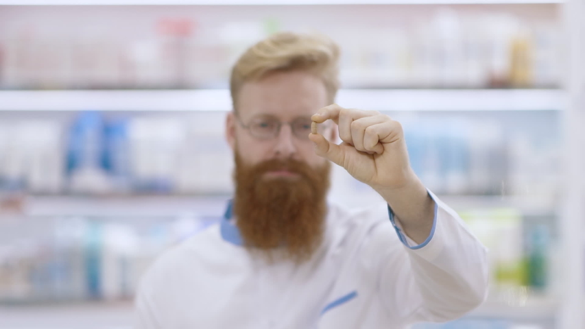 Young doctor or pharmacist shows a pill and nods his head approvingly   Shutterstock HD Video #1047126841