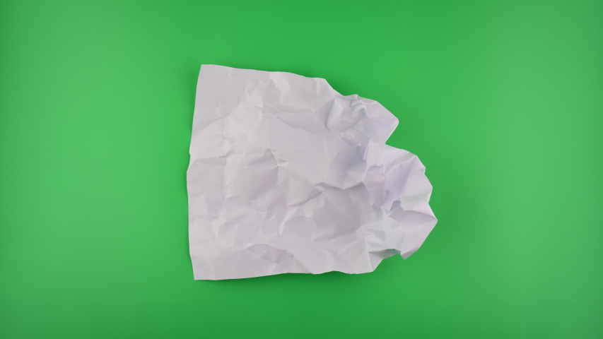 Stop motion VDO, paper ball unwrapping on green background.
