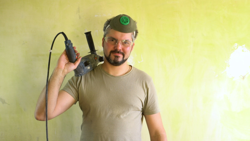 A man in glasses and a protective mask is standing by the wall. Holds a hammer drill on his shoulder. On the face is a beard. Shows a thumb gesture. Construction site. Portrait to the waist.  | Shutterstock HD Video #1047134656
