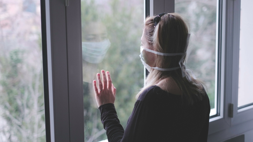 Woman at window with a mask in isolation for virus outbreak . | Shutterstock HD Video #1047139360