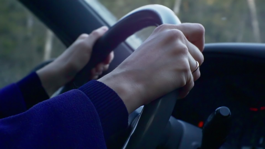 Close-Up of woman's Hands on Car Steering Wheel. #1047149458