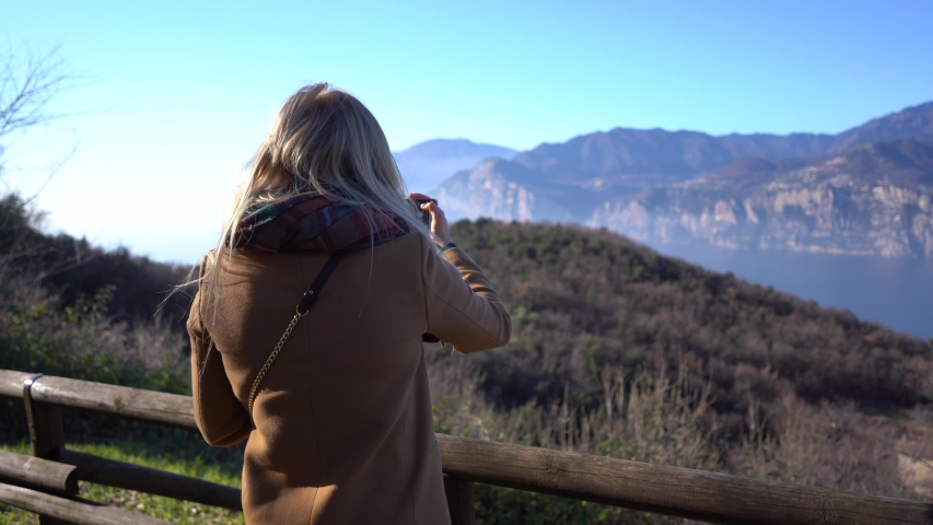 Woman is taking pictures of a beautiful mountain vive   | Shutterstock HD Video #1047163939
