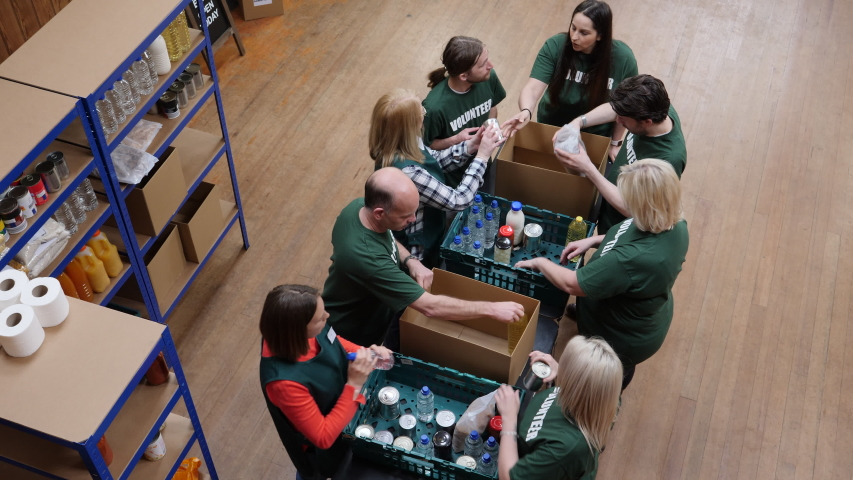 4K: Food Bank volunteers sorting food into boxes for hungry people and with social issues. Overhead View. Looking down from above,