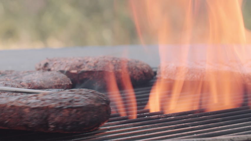 Vegan plant based burger meat on flaming hot grill   Shutterstock HD Video #1047170017