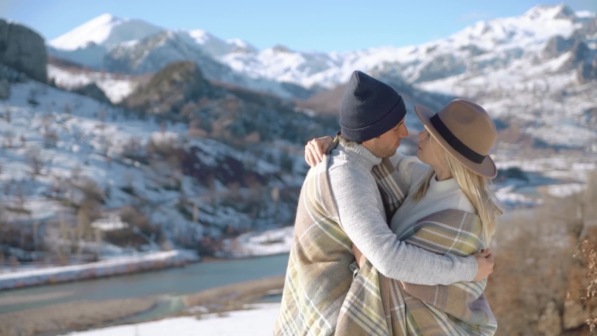 Young couple hugging with beautiful snowy mountains on background. Slow motion. Portrait view. | Shutterstock HD Video #1047170257