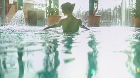 Wellness - white woman in her 30s enjoying water in pool, smiling.