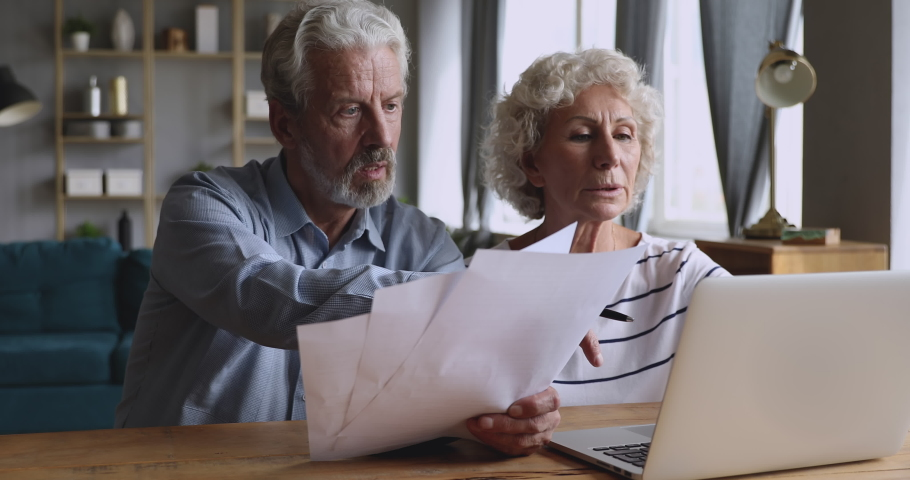 Focused middle aged man holding paper documents, helping pleasant attractive mature wife filling information in online banking app on computer. Serious older couple managing family budget at home.