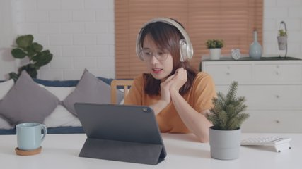 Pretty Young Asian Woman wearing headphones looking at a digital tablet screen Video call learning online on internet, listening and chatting with online teacher or chatting with her friend.