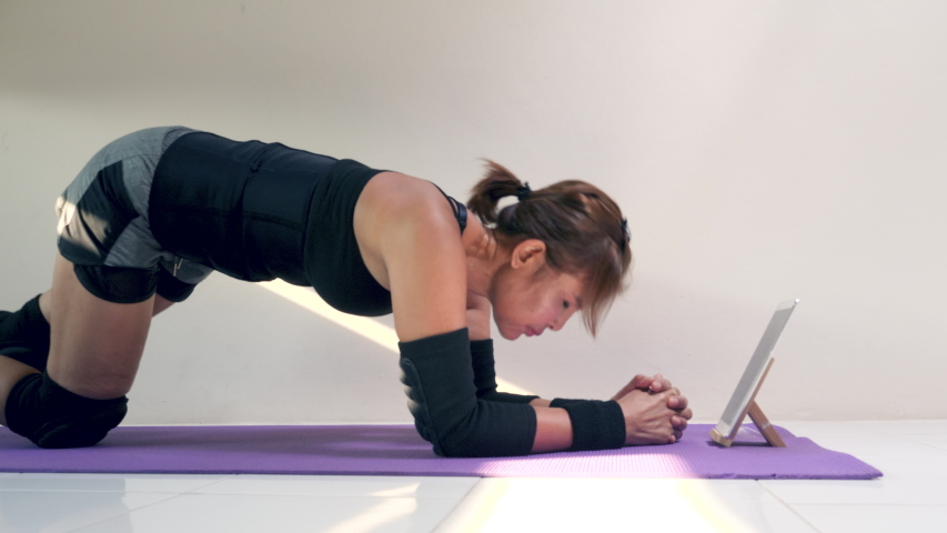 Asian 59 years old woman watching video on tablet while working out with exercise equipment at home. Healthy lifestyle, recreation, keeping in shape. Attractive Muscular Female Battling Workout.