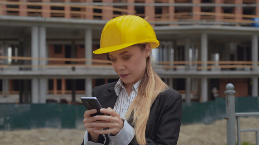 Portrait of a young girl in a business engineer insuit and a yellow hard construction hat. female on the background of the construction site is using a mobile phone typing a text message 4K Royalty-Free Stock Footage #1047194785