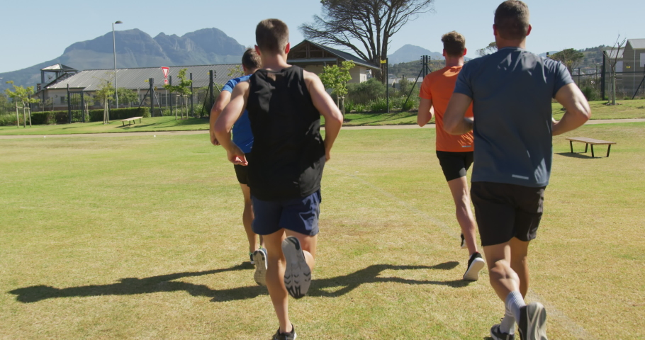 Rear view of a multi-ethnic group of male runners training at a sports field, running together on a grass track. Track and Field Sports Training in Stadium, in slow motion #1047200290
