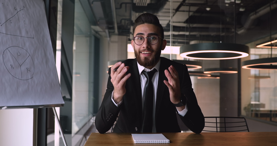 Motivated successful young arabic businessman in eyeglasses sitting at office desk, looking at camera. Smiling pleasant middle eastern ethnicity male speaker coach trainer recording educational video.