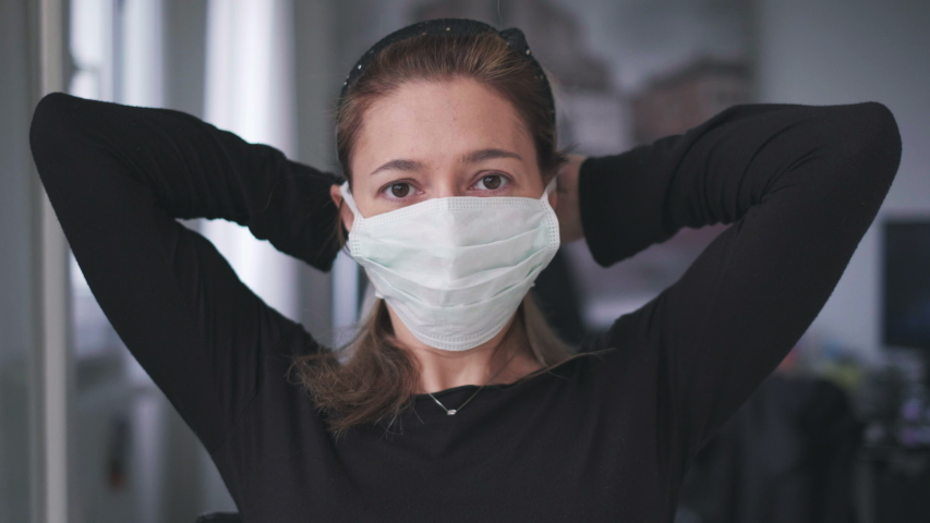 Woman putting on surgical mask for corona virus prevention.