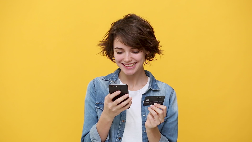 Smiling woman in denim jacket white t-shirt posing isolated on yellow background in studio. People sincere emotions, lifestyle concept. Looking using mobile phone hold credit bank card online shopping Royalty-Free Stock Footage #1047209044