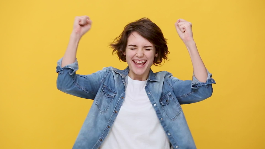 Smiling overjoyed beautiful brunette young woman in denim jacket white t-shirt posing doing winner gesture, say Yes isolated on yellow background in studio. People sincere emotions, lifestyle concept
