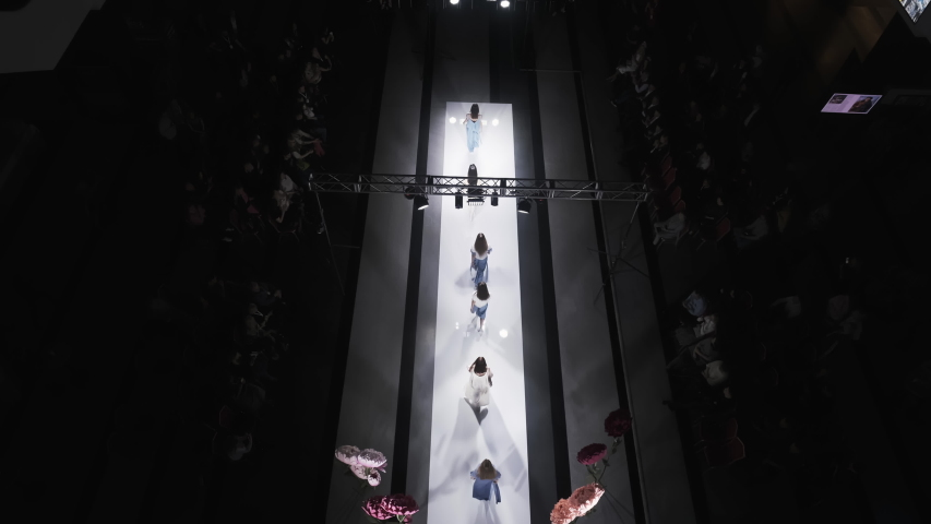 Defile attractive girl in colorful dress on catwalk model show closeup evening vogue 4K. Fashion design modern clothes woman on podium slow motion spotlights stage. | Shutterstock HD Video #1047211297