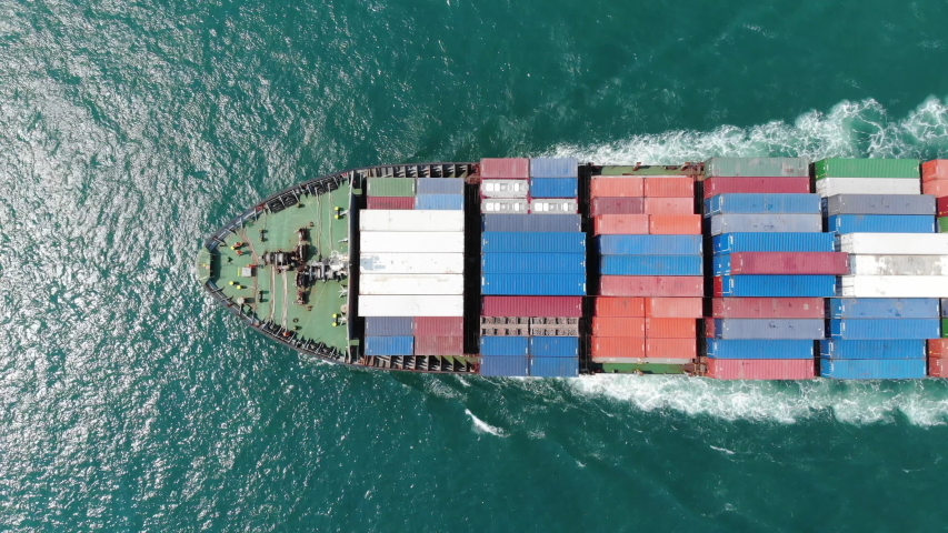Aerial of smart cargo ship carrying container and running for export  goods  from  cargo yard port to other ocean concept freight shipping ship on blue sky background.