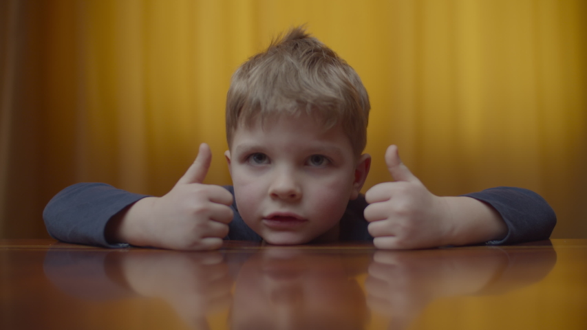 Portrait of blonde preschool boy smiling and looking to camera. Kids head on the table at home. Smiling kid shows thumbs up.  Royalty-Free Stock Footage #1047212017