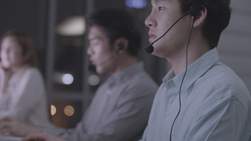 Service phone operator sit at shared desk at night.Focus on man in headsets with microphones sitting before computers in office looking at the screen,typing and talking on voice calls.Business concept